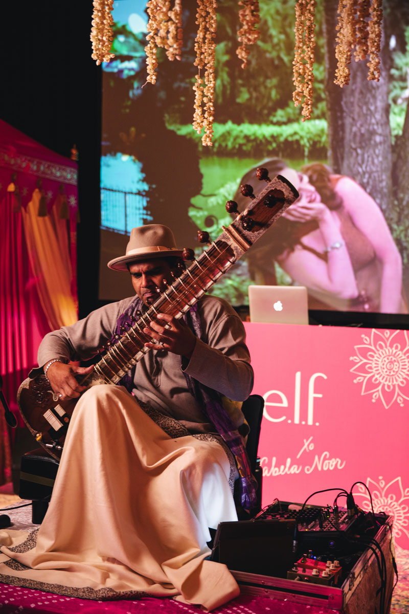 Man plays sitar at Indian themed wedding event