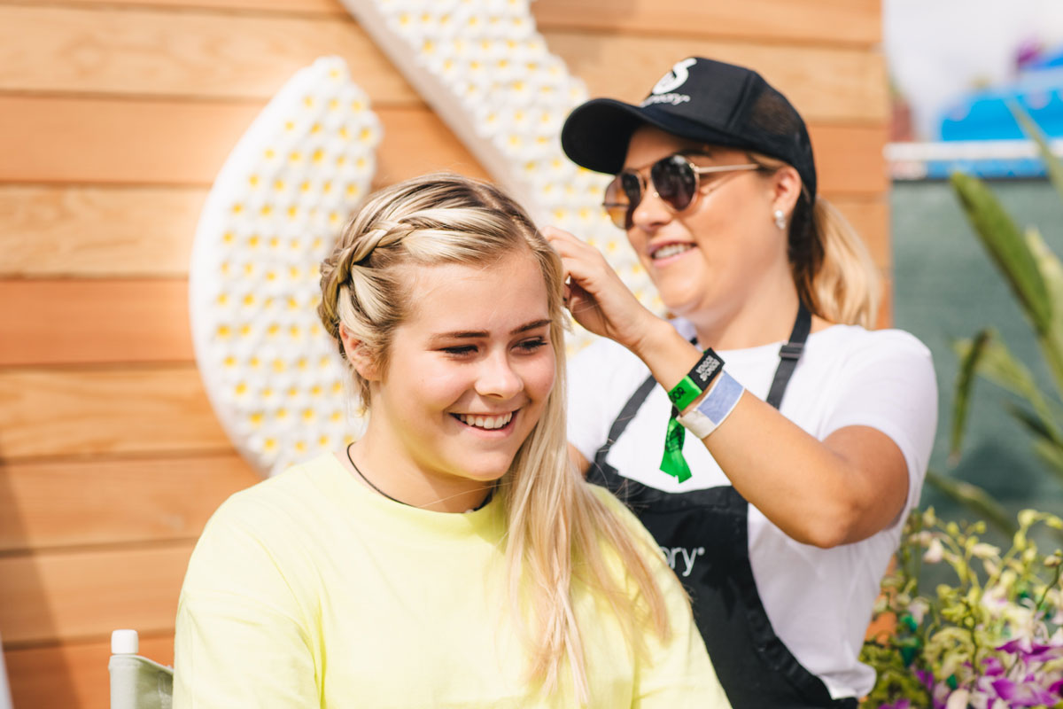 Young woman getting hair braided