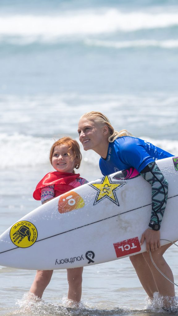 Surfer Tatiana Weston-Webb with young girl in cape